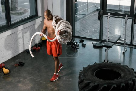 high angle view of shirtless muscular african american athlete with battle rope at gym