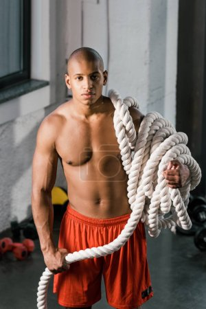 Photo for Muscular african american athlete with battle rope at gym - Royalty Free Image