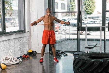 Photo pour Jeune athlète afro-américain, faire des exercices avec la bande d'élongation au gymnase - image libre de droit