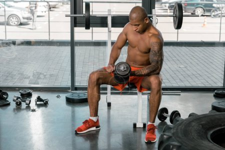 tattooed muscular african american sportsman exercising with dumbbell at gym