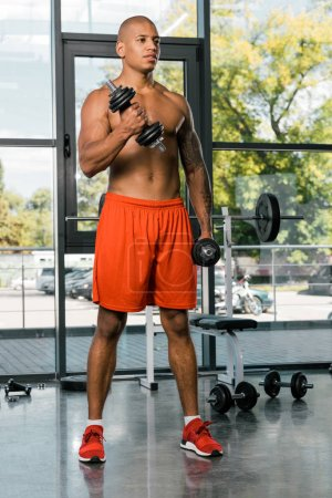 selective focus of muscular shirtless african american sportsman exercising with dumbbells at gym