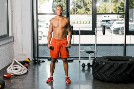 young african american sportsman exercising with dumbbells at gym