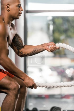 side view of african american athlete working out with battle ropes at gym