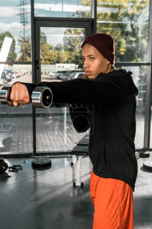 young african american male boxer practicing with dumbbells at gym