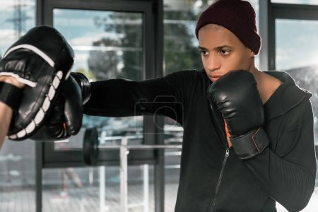 young african american boxer in boxing gloves practicing with trainer at gym