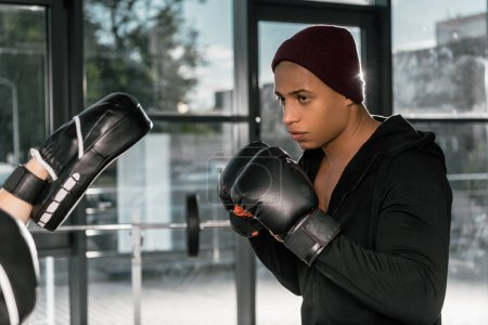 serious african american boxer in boxing gloves practicing with trainer at gym