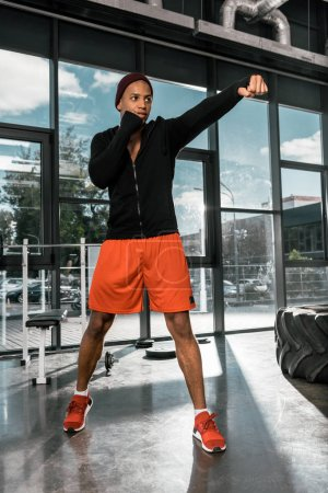 low angle view of young african american boxer exercising at gym