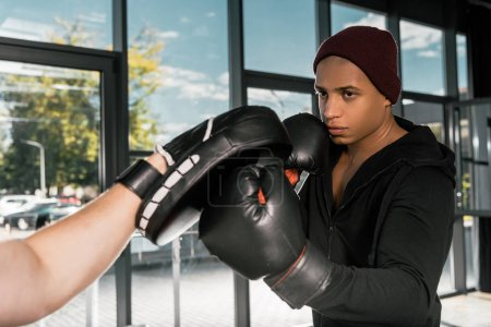 confident african american boxer in boxing gloves practicing with trainer at gym