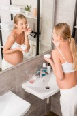 high angle view of happy pregnant woman applying facial cream in front of mirror in bathroom