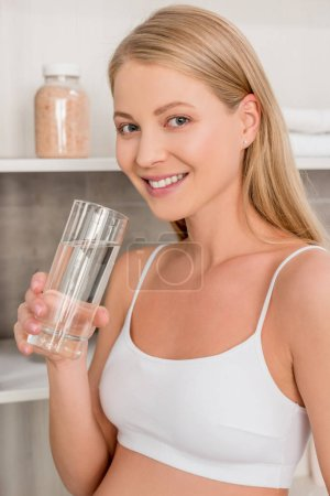 close-up portrait of pregnant woman with glass of water looking at camera in bathroom