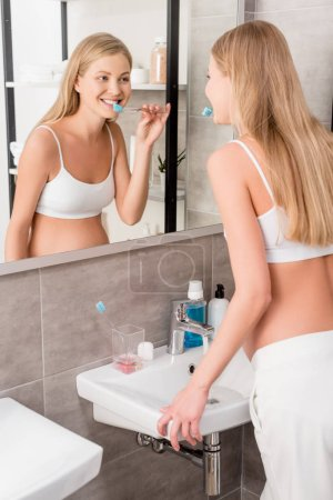 attractive pregnant woman looking at mirror and brushing teeth in bathroom