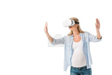 Foto de Mujer embarazada expresiva en realidad virtual auricular gesticular con las manos aisladas en blanco - Imagen libre de derechos