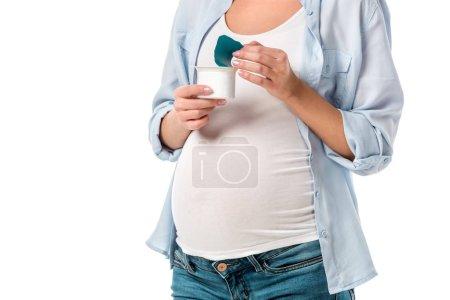cropped shot of pregnant woman holding yogurt isolated on white