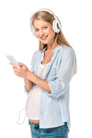 smiling pregnant woman listening music with headphones and smartphone isolated on white