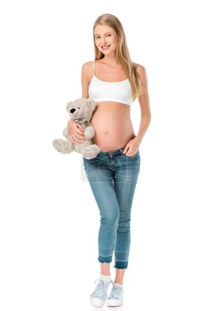 smiling pregnant woman in jeans holding teddy bear isolated on white