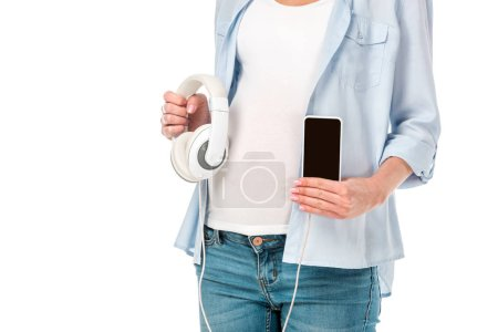 cropped view of pregnant woman holding headphones and showing smartphone with blank screen isolated on white