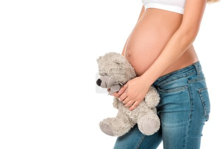 cropped view of pregnant woman holding teddy bear near her belly isolated on white