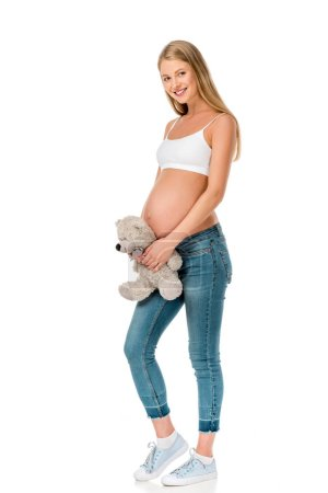 beautiful smiling pregnant woman holding teddy bear isolated on white