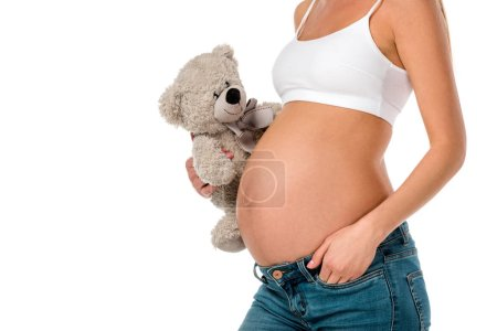 cropped view of pregnant girl in white bra holding teddy bear isolated on white