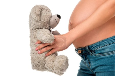 partial view of pregnant girl holding teddy bear in front of belly isolated on white