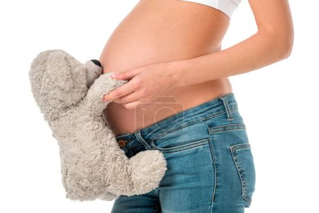 cropped view of pregnant girl holding teddy bear at her tummy isolated on white