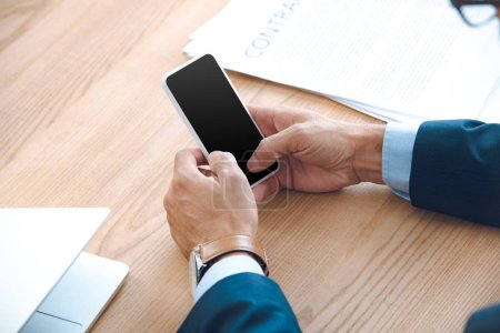 cropped shot of businessman using smartphone with blank screen at workplace