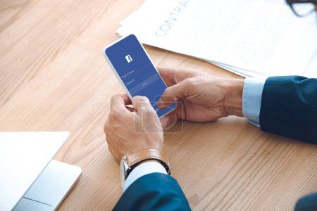 Photo for Cropped shot of businessman using smartphone with facebook application on screen - Royalty Free Image