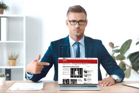 handsome businessman in eyeglasses pointing at laptop with bbc news website on screen