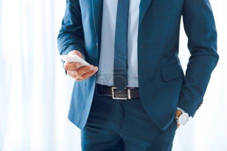 Photo pour Recadrée tir d'homme d'affaires en tenues à l'aide de smartphone - image libre de droit