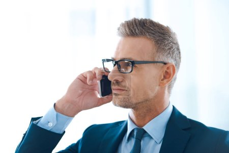 handsome confident businessman in eyeglasses talking by smartphone and looking away in office