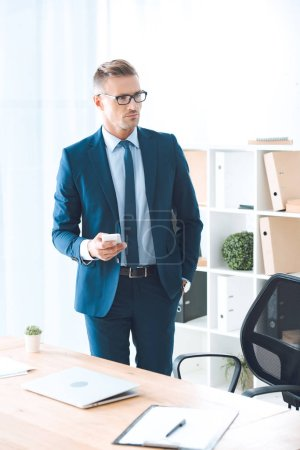confident businessman in eyeglasses holding smartphone and looking away in office