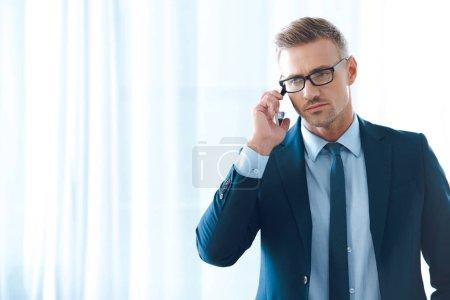 serious businessman in eyeglasses talking by smartphone and looking away