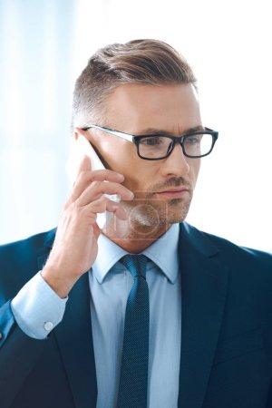 Photo pour Bel homme d'affaires en lunettes de vue parler de smartphone et de loin à la recherche - image libre de droit