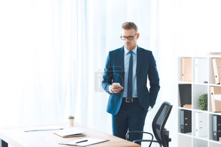 handsome businessman in eyeglasses and formal wear using smartphone at workplace