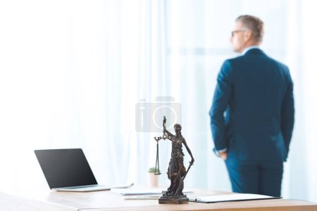 Photo pour Ordinateur portable blanc écran et Dame justice statue sur la table et avocat en regardant la fenêtre derrière - image libre de droit