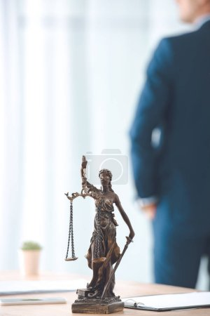 close-up view of lady justice statue and lawyer standing behind