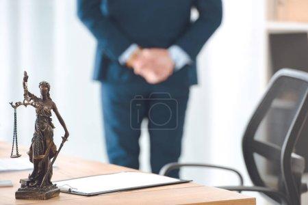 Photo pour Vue rapprochée de Dame justice statue et presse-papiers sur table et avocat debout derrière - image libre de droit