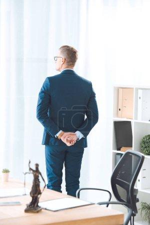 Photo pour Vue d'avocat permanent au bureau et en regardant la fenêtre arrière - image libre de droit