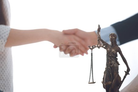 close-up view of lady justice statue and lawyer with client blank shaking hands behind