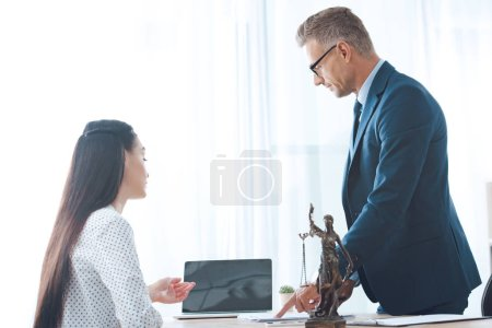 lawyer and young female client using laptop in office