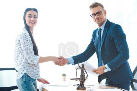 Photo pour Avocate professionnelle et jeune cliente serrant la main et souriant à la caméra - image libre de droit