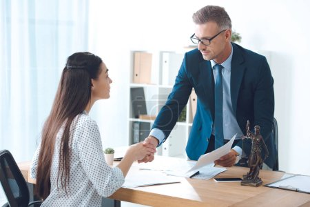 professional lawyer and young female client shaking hands in office