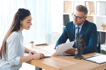 smiling lawyer showing papers to happy client in office