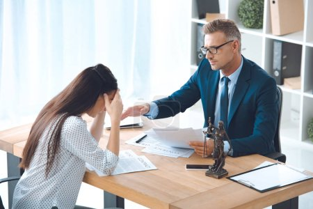 lawyer working with upset female client in office