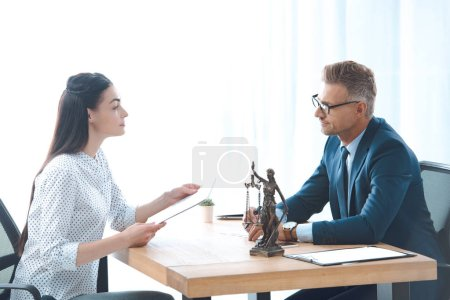 side view of lawyer and client discussing papers in office