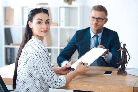 Photo pour Souriant avocat tenant presse-papiers tandis que la jeune femme signer des papiers et en regardant la caméra - image libre de droit