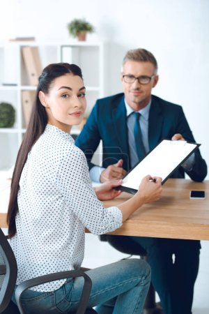 lawyer holding clipboard while female client signing contract and smiling at camera