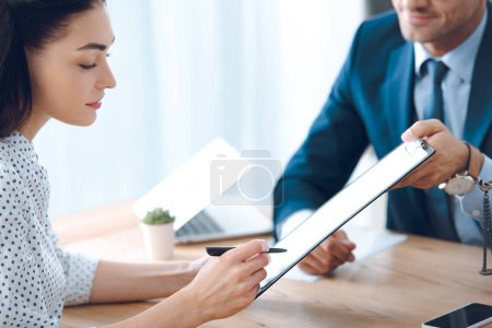 Photo for Cropped shot of lawyer holding clipboard and young woman signing document - Royalty Free Image