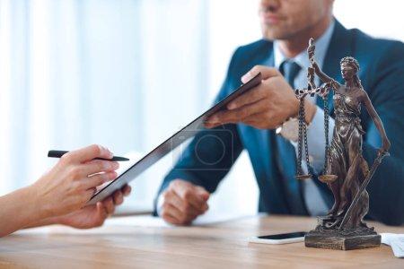 Photo pour Recadrée tir d'avocat détenant le presse-papiers et le client signant le document - image libre de droit