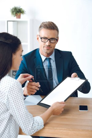 handsome lawyer in eyeglasses giving clipboard with document and pen to female client